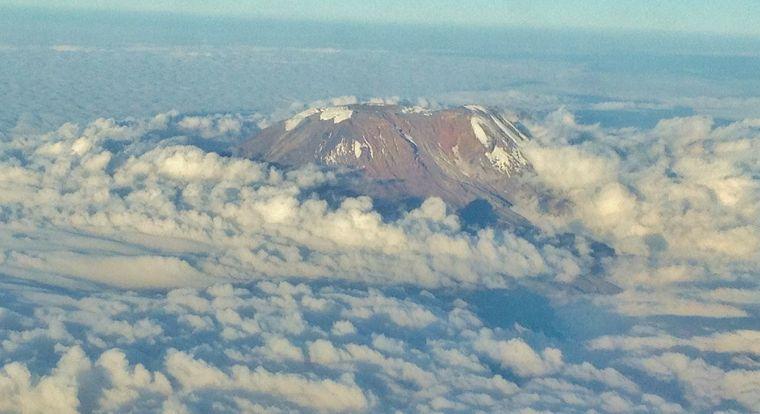 Die Bergspitze des Kilimanjaro ragt aus einer Wolkeninsel empor.