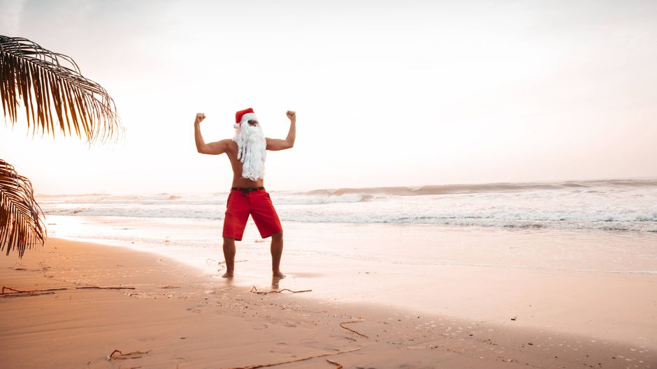Ein Mann ist in Thailand als Weihnachtsmann verkleidet am Strand.