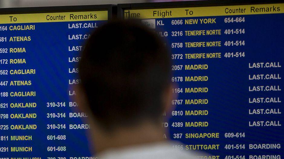 Menschen vor einer Anzeigetafel am Flughafen von Barcelona.