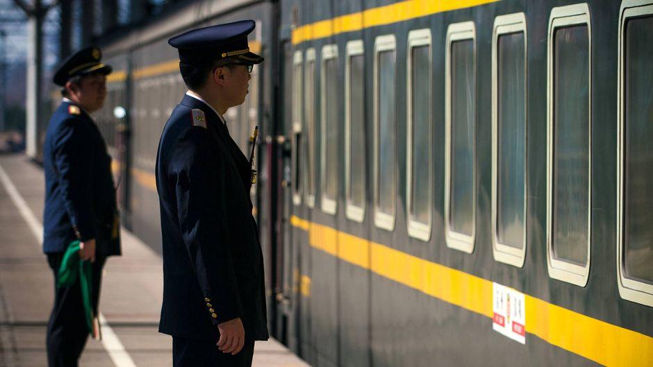 Zwei Zugbegleiter stehen an einem Bahnsteig in China.