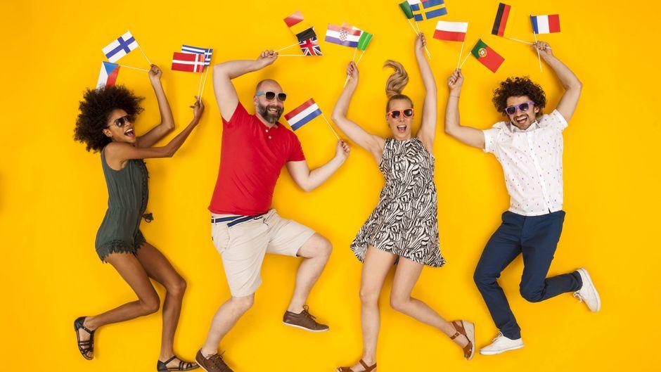 Eine Gruppe junger Leute tanzt mit Flaggen europäischer Länder