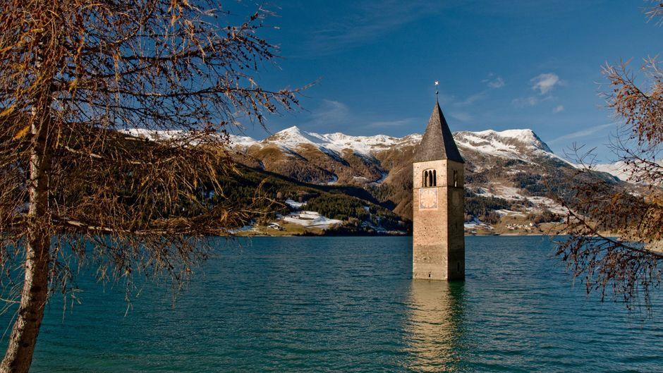 Kirchturm der ehemaligen Pfarrkirche Sankt Katharina von Graun im Reschensee, Vinschgau, Südtirol.