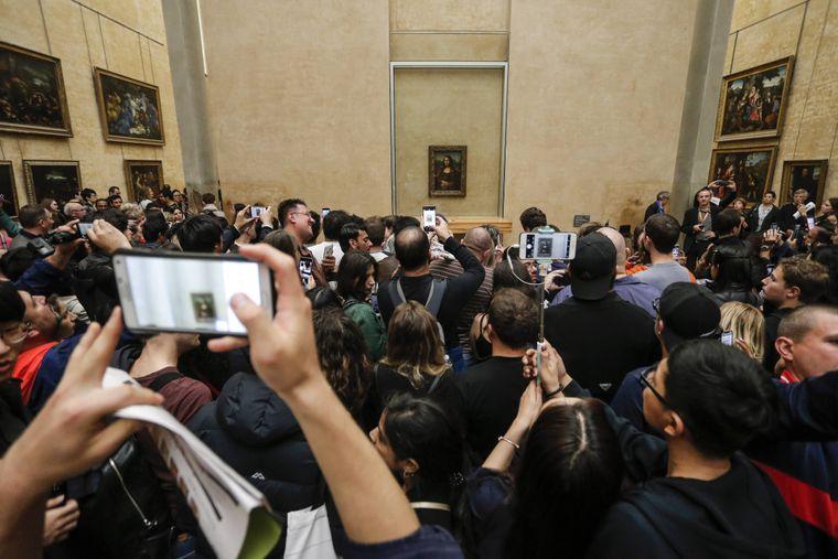 Menschen versuchen im Louvre Fotos von der Mona Lisa zu machen.
