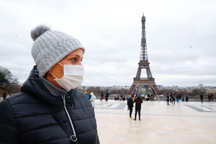 Touristin mit Gesichtsmaske vor dem Eiffelturm in Paris.