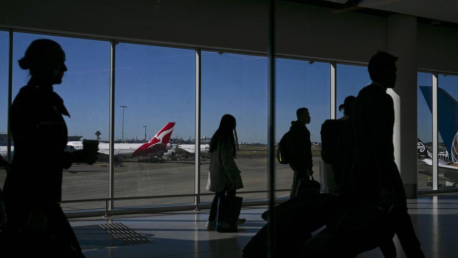 Passagiere am Flughafen Sydney, im Hintergrund steht ein Flugzeug der Airline Qantas.