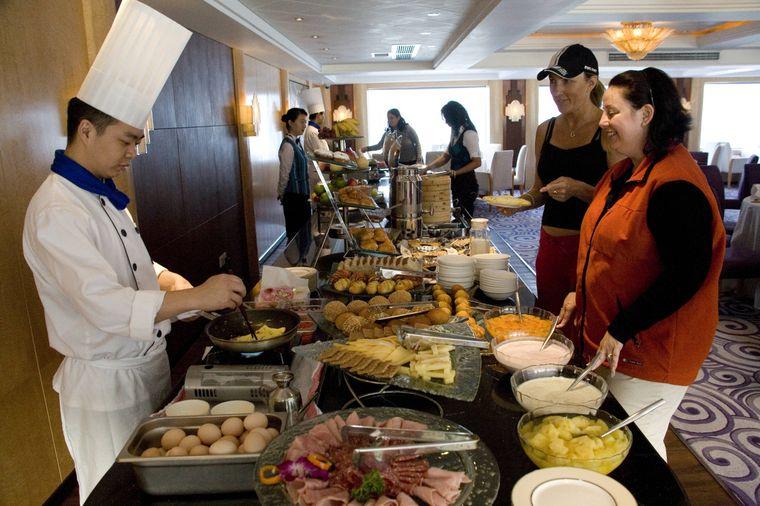 Ein Koch bereitet Omelettes für Gäste auf einem Kreuzfahrtschiff zu.