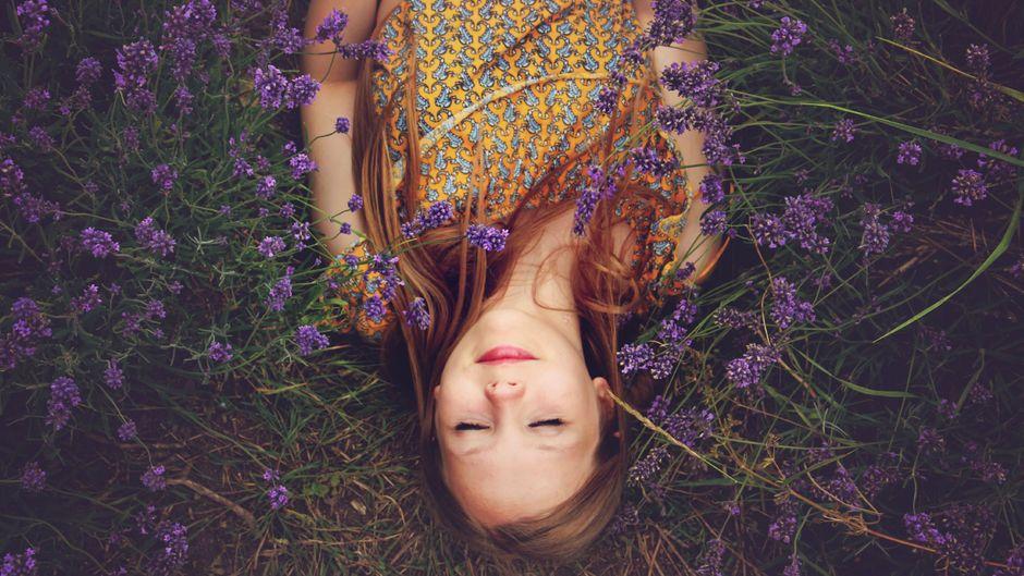 Eine Frau genießt die Ruhe in einem Lavendelfeld und hört.