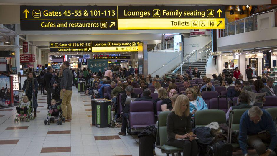 Menschen warten im Abflugbereich des Flughafens Gatwick in London.