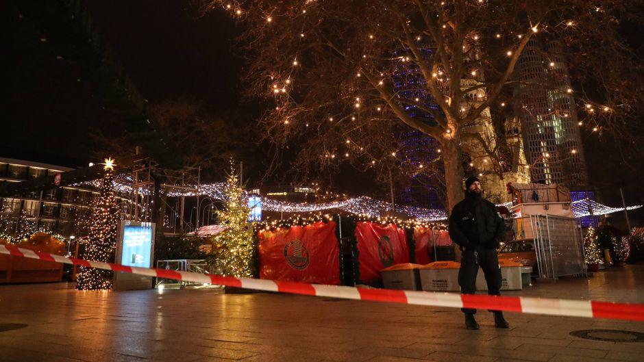 Ein Polizist steht nach dem mutmaßlichen Anschlag vor dem Weihnachtsmarkt am Breitscheidplatz an der Gedächtniskirche hinter einem Absperrband.