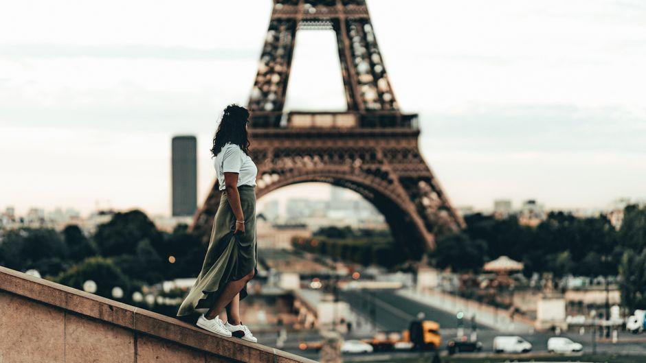 Ein Mädchen blickt auf den Eiffelturm in Paris.