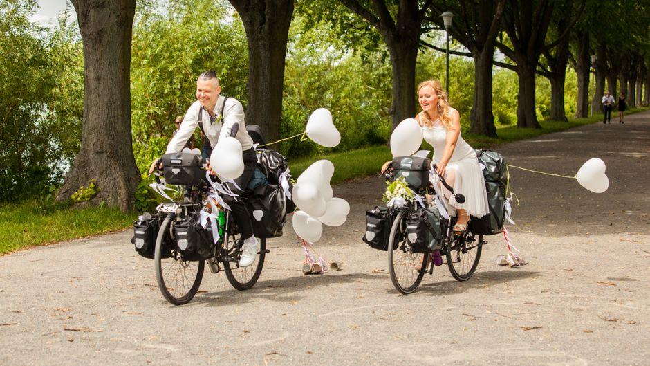 Oliver und Helena Wilhelm an ihrem Hochzeitstag auf Fahrrädern am Maschsee in Hannover.
