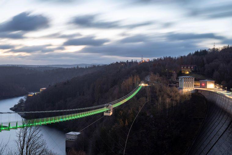 Die in der Abenddämmerung beleuchtete Hängebrücke Titan RT an der Rappbodetalsperre im Harz.