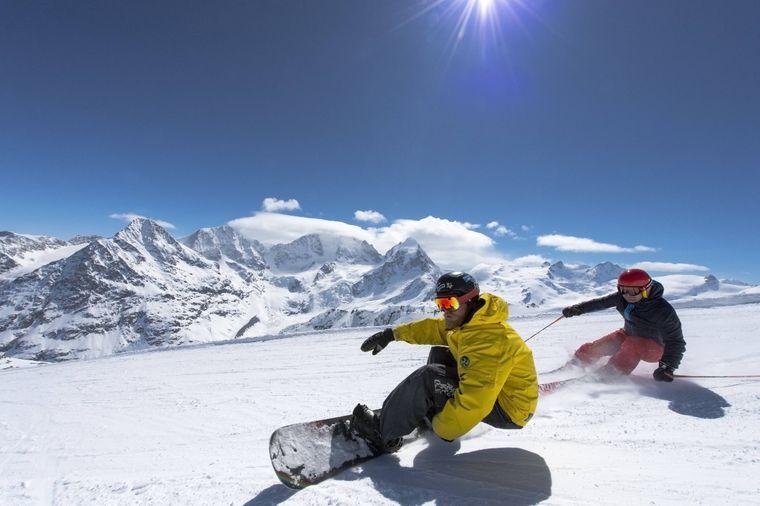 Skifahrer und Snowboarder sind rasant auf der Piste unterwegs. Hinter ihnen das Bernina-Massiv.