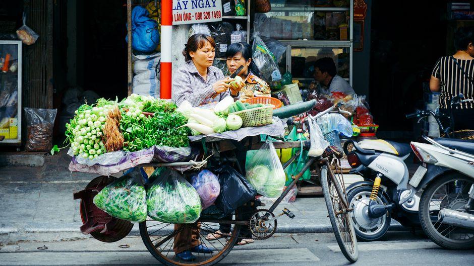Eine Frau verkauft Lebensmittel auf einer Straße in Hanoi, Vietnam.
