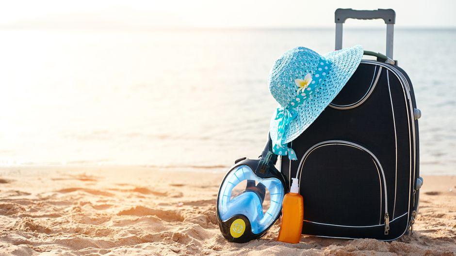 Koffer, Hut und Schnorchelmaske am Strand.