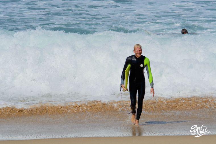 Stephan geht mit seinem Surfbrett vom Meer über den Strand.