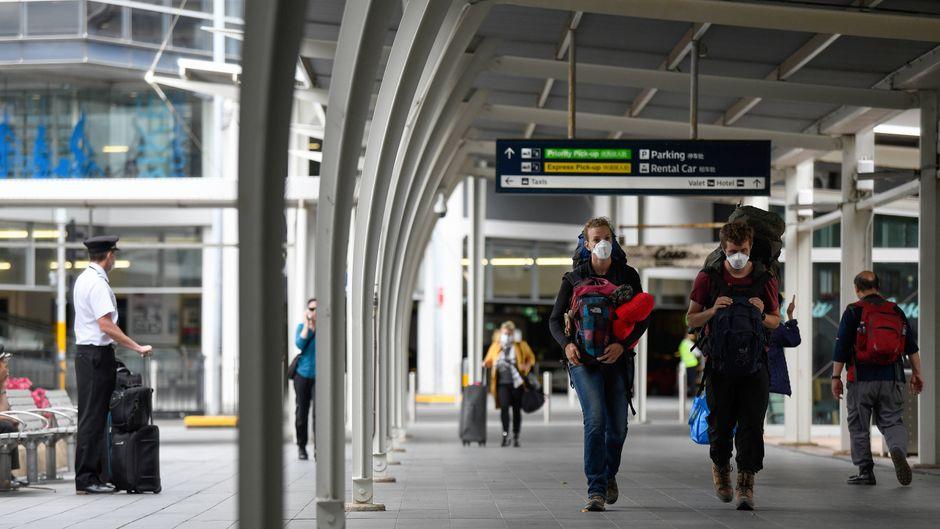 Reisende mit Mundschutz am Flughafen von Sydney.