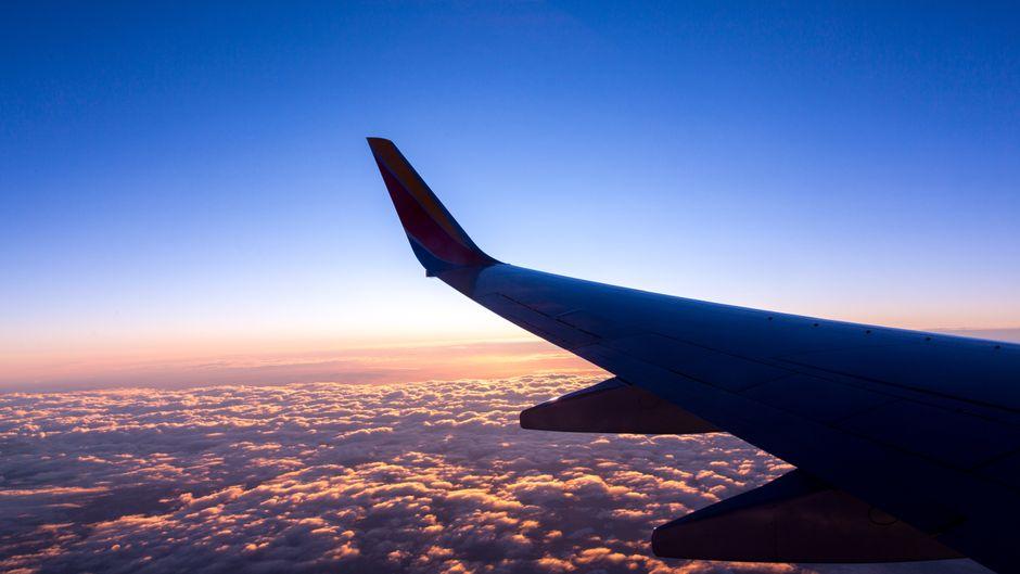 Flügel eines Flugzeugs bei Sonnenuntergang über den Wolken.