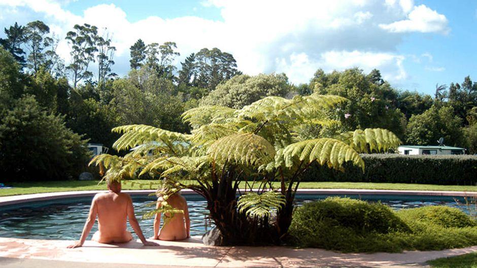 Ein nackter Mann und eine nackte Frau sitzen am Pool.