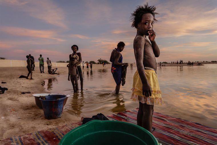 Einwohner in Timbuktu baden und waschen Wäsche im Hafen von Kabara im letzten Licht des Tages.