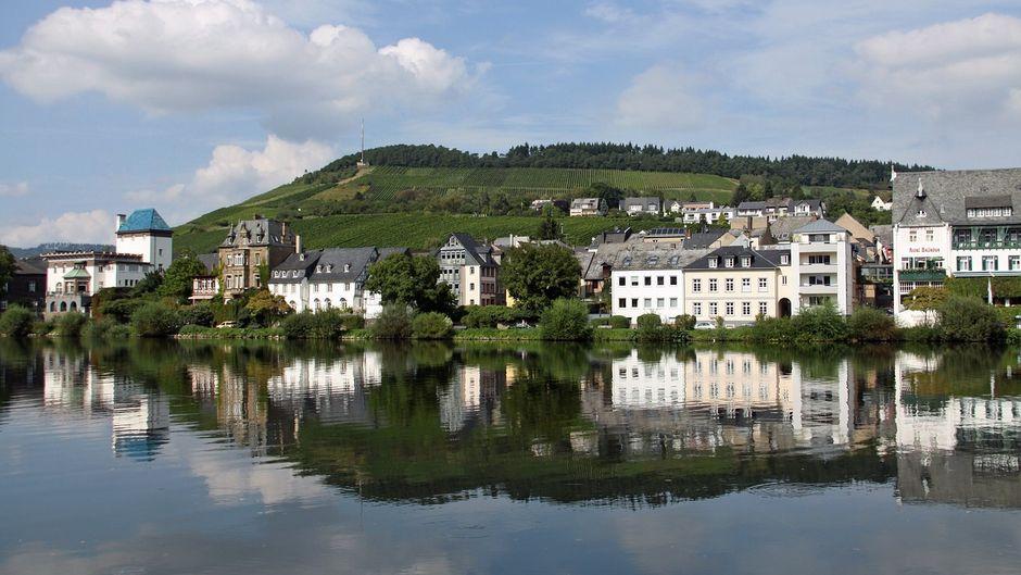Im Wasser spiegelt sich die schöne Stadt Traben-Trabach, die direkt an der Mosel liegt. Hier fließt aber nicht nur der Fluss, sondern auch jede Menge Wein in die Köpfe der Urlauber und Einwohner hinein.