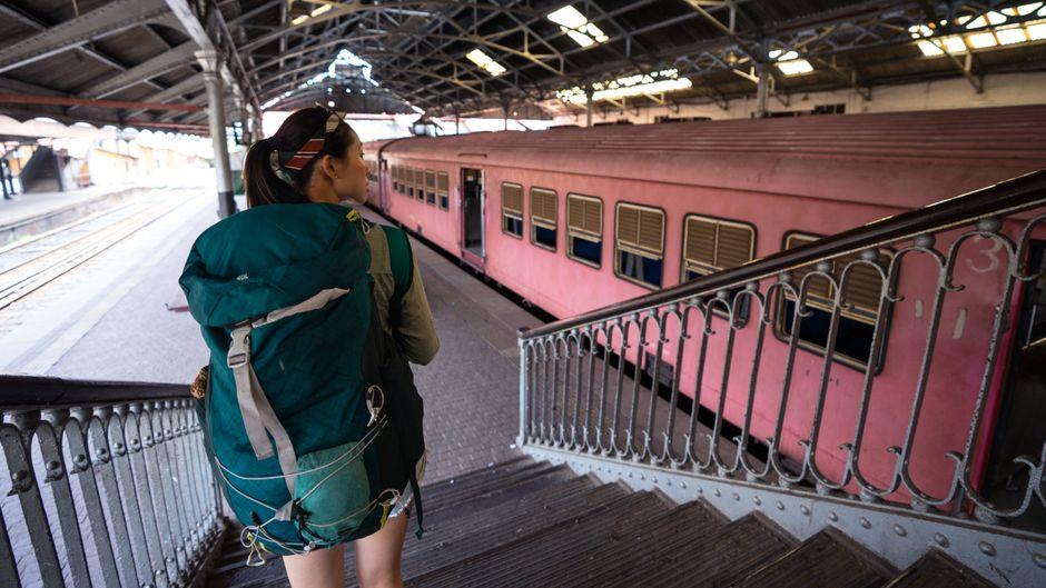 Ohne Flugzeug auf Reisen: Eine Frau mit Rucksack steigt eine Treppe an einem Bahnhof hinab. (Symbolfoto)