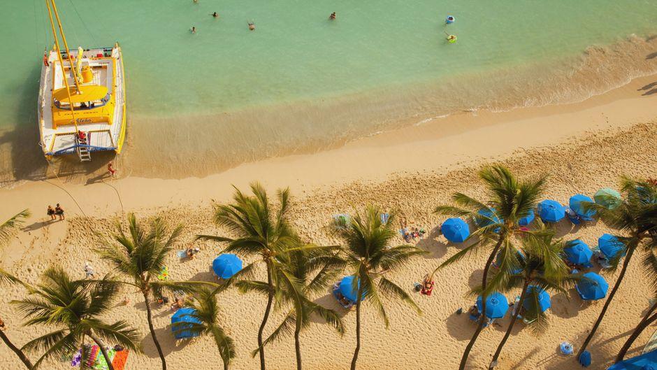 Palmen und ein Boot am Waikiki Beach in Honolulu auf O'hahu in Hawaii.