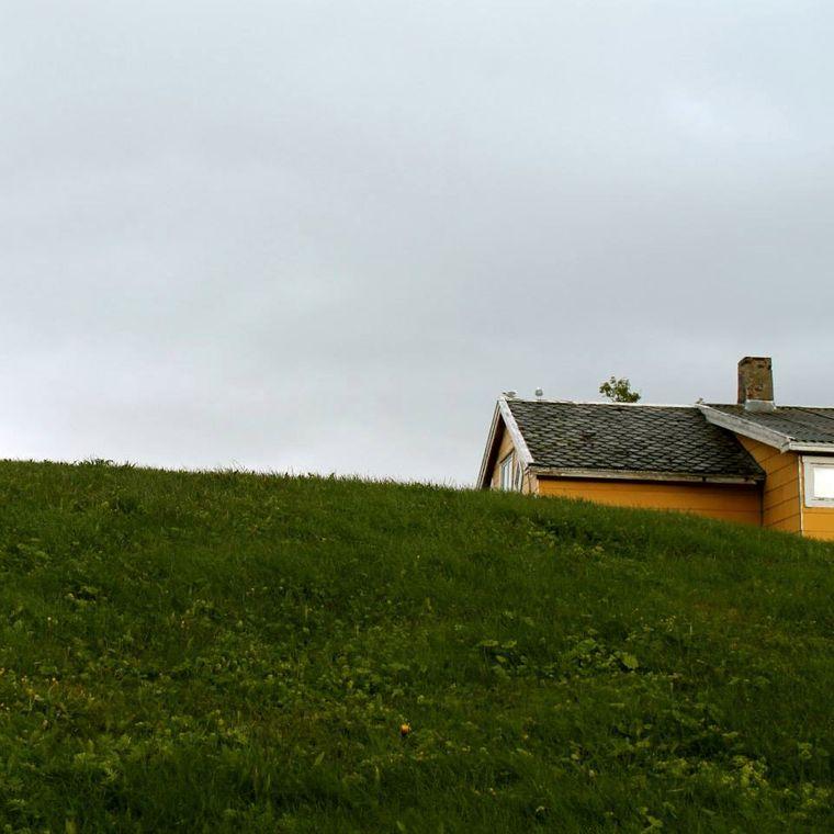 Auf Sommarøya stehen bunte Holzhäuser zwischen grünen Hügeln.