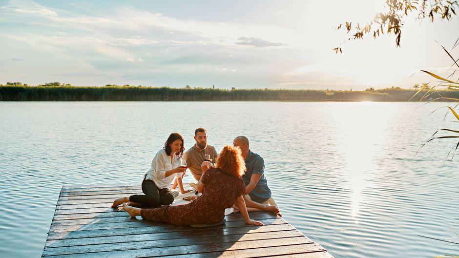 Eine Gruppe junger Leute bei einem Picknick am See. Spanien gilt als Corona-Risikogebiet, Urlauber müssen danach in Deutschland in Quarantäne.