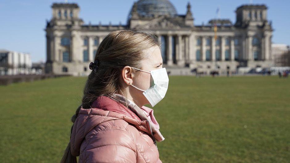 Frau mit Mundschutz vor dem Bundestag in Berlin.