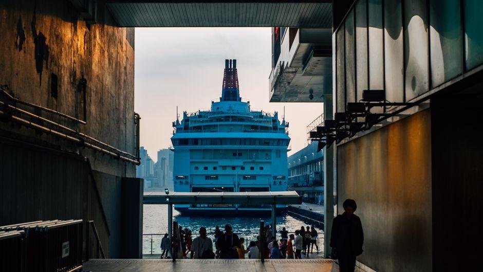 Menschen stehen vor einem Kreuzfahrtschiff.