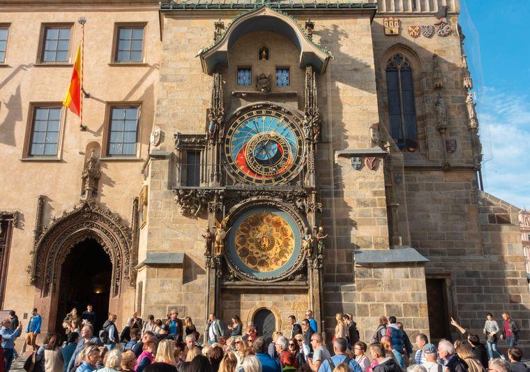 Touristinnen und Touristen stehen dicht gedrängt vor der Prager Rathausuhr.