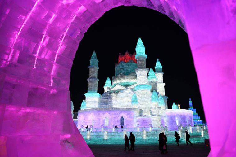 Ein hell erleuchtetes Schloss aus Schnee und Eis beim Eisskulpturen-Festival in Harbin, China.