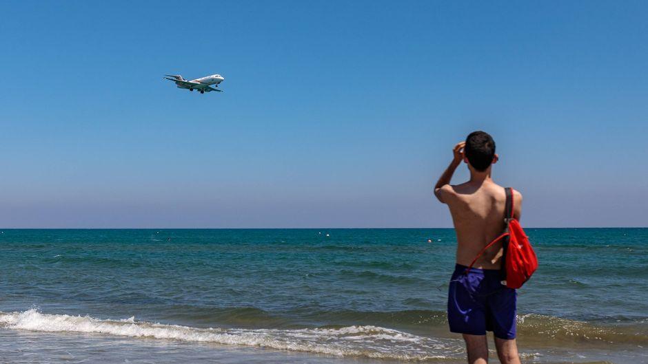 Touristen am Strand beobachten die Landung eines Passagierflugzeugs.