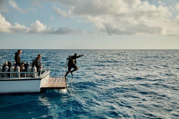 Taucher springen vom Boots in Meer, Bahamas.