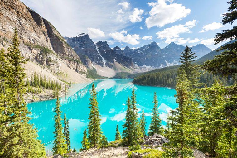 Im türkisfarbenen Moraine See spiegeln sich die schneebedeckten Bergen des Banff Nationalparks