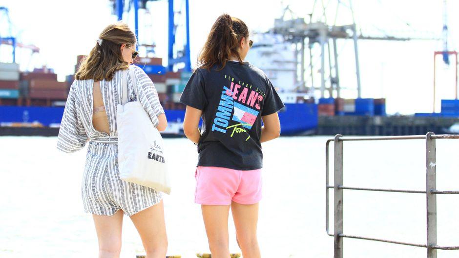 Zwei junge Frauen stehen am Schiffsanleger Övelgönne in Hamburg und warten auf eine Fähre.