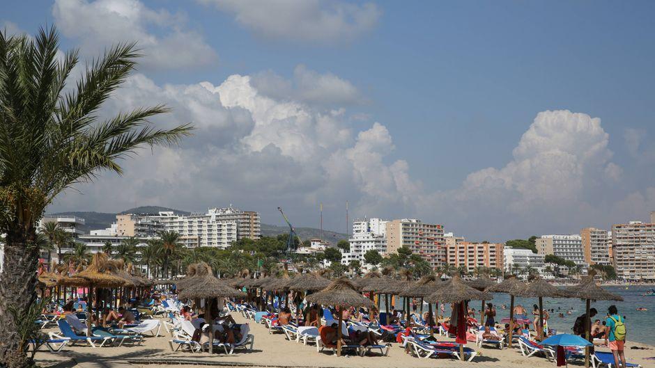 Im Vordergrund Liegen an einem Strand in Magaluf, im Hintergrund stehen Hotelanlagen.