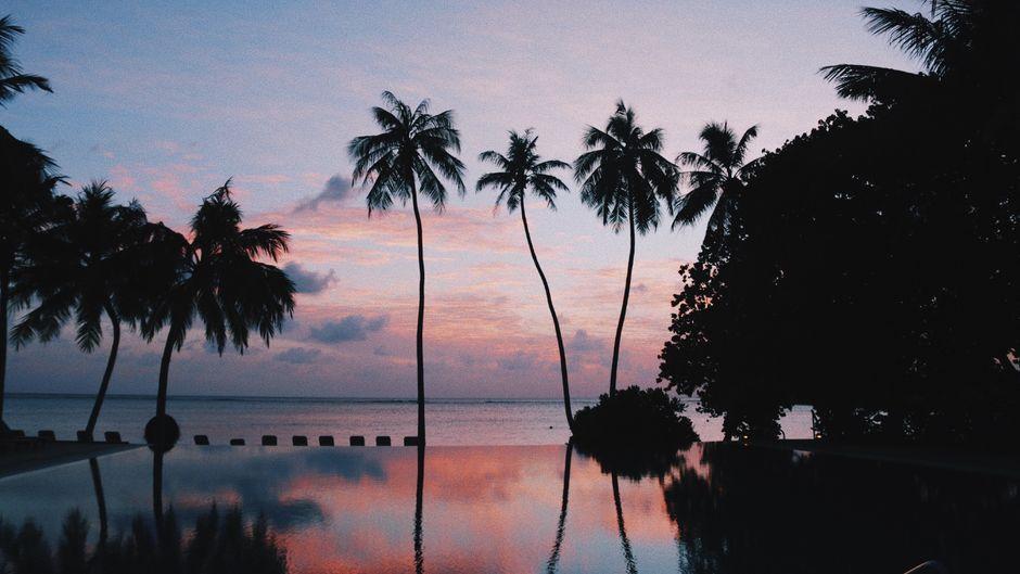 Infinity-Pool am Strand bei Sonnenuntergang.