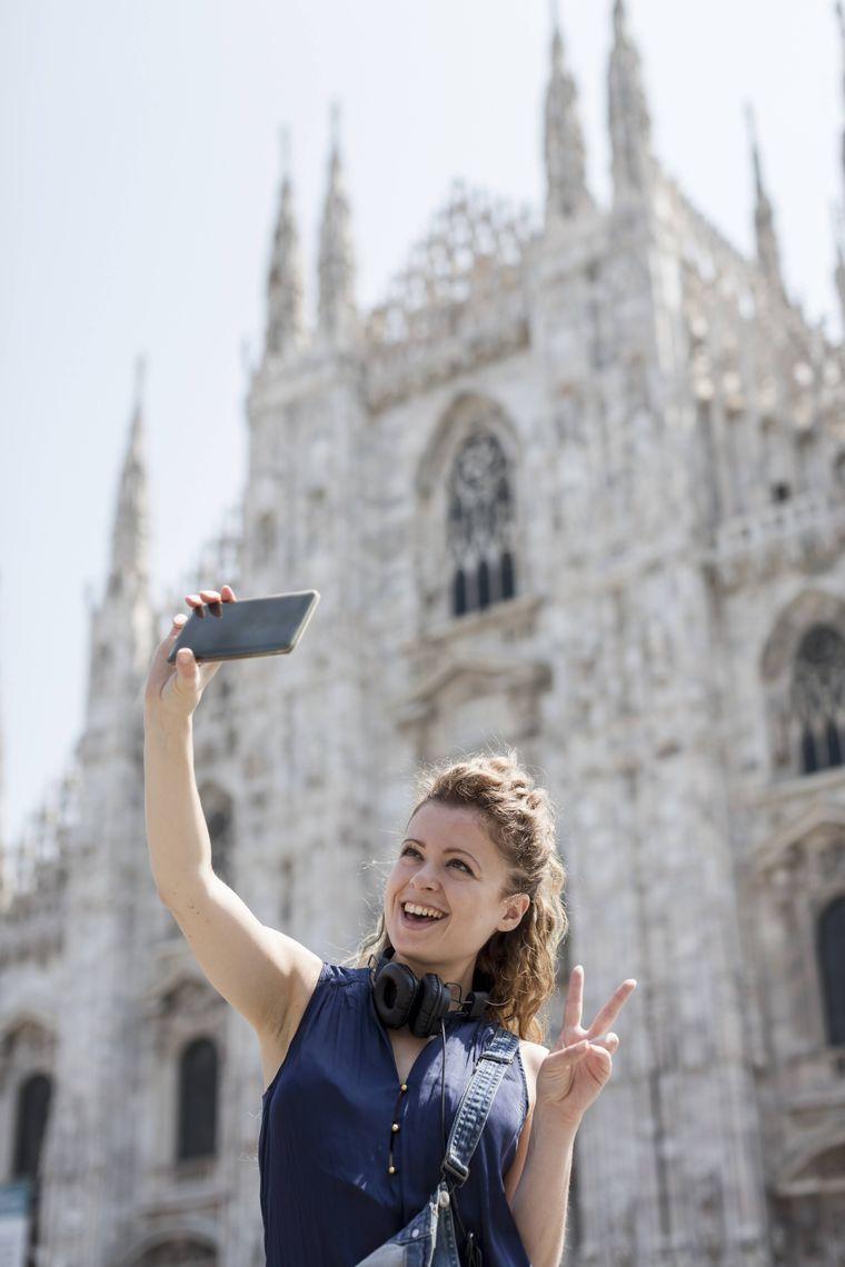 Frau macht ein Selfie vor dem Dom in Mailand.