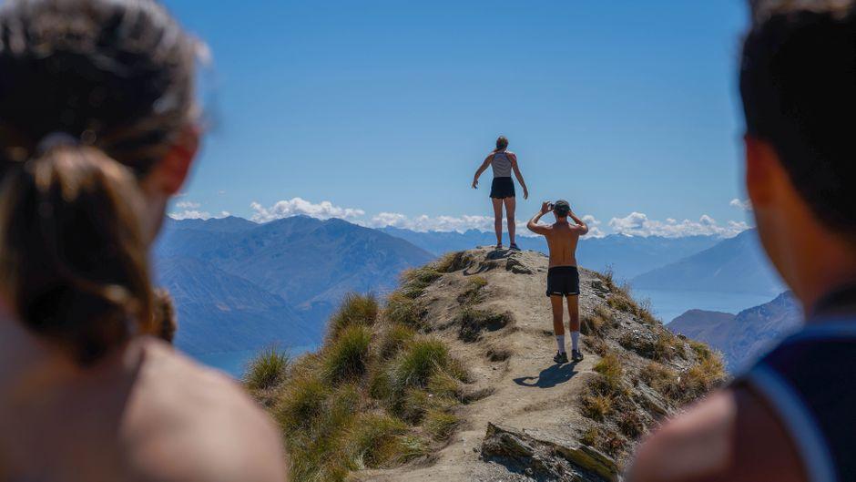 Vier Menschen stehen auf dem Roys Peak in Neuseeland und machen ein Foto für Instagram.