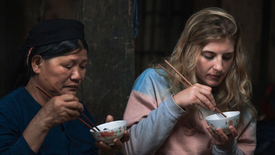 Touristin isst mit Einheimischer und traditionellem Besteck.