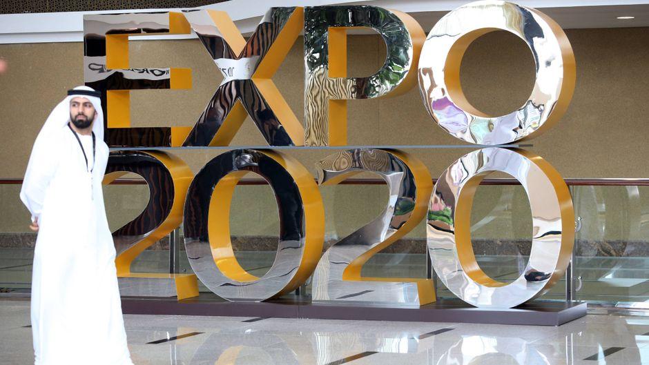 Ein Mann vor einem Werbeaufsteller für die Expo 2020 in Dubai.