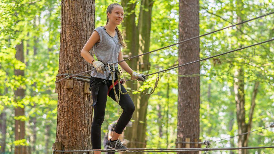 Eine Frau überwindet Hindernisse in einem Kletterwald. (Symbolfoto)