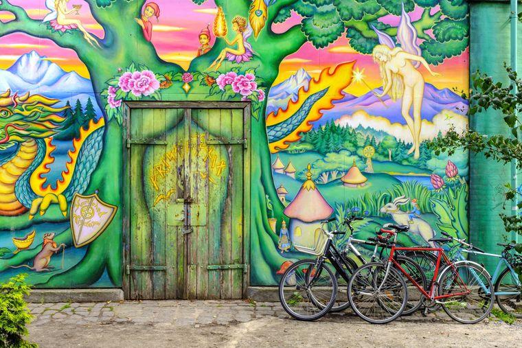 Bunt bemalte Hauswand in Christiania in Kopenhagen, davor Fahrräder.
