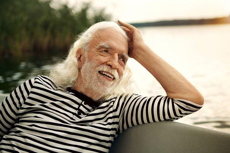Porträt eines Mannes, der sich auf einem Boot anlehnt.