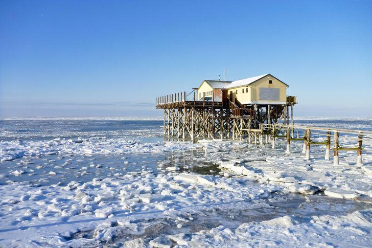 """Die Strandbar in der Nordseestadt St. Peter-Ording """"54 Grad Nord"""" zwischen Eisschollen."""