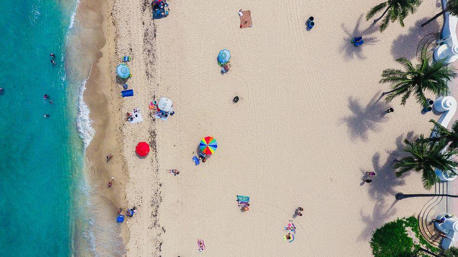 Menschen liegen am Strand und baden im Meer