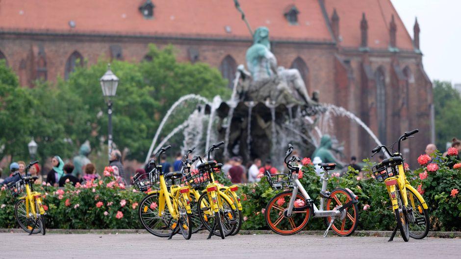 Leihfahrräder verschiedener Anbieter stehen vor dem Neptunbrunnen in Berlin-Mitte.