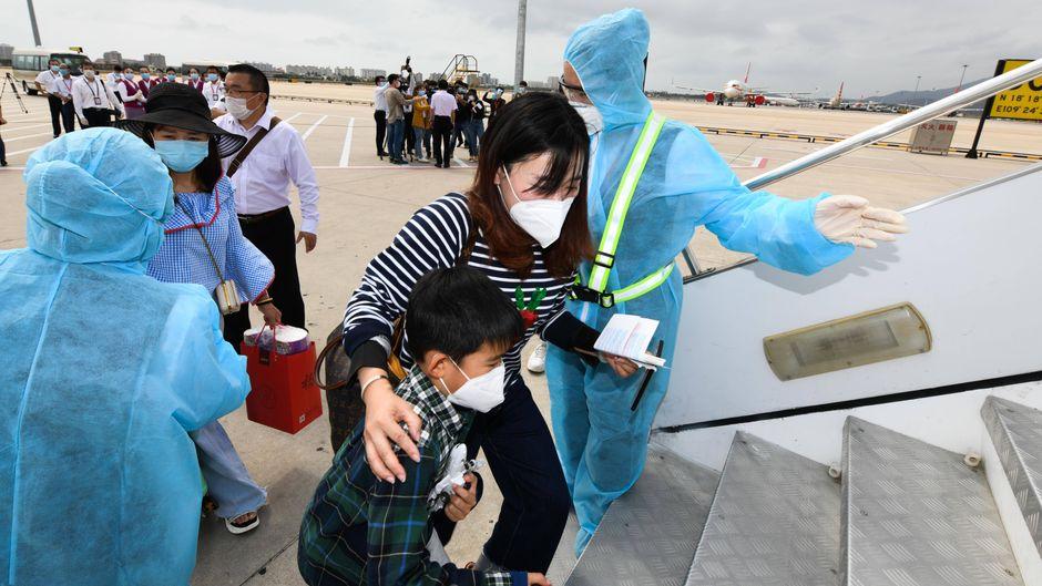 Passagiere in Sanya in China steigen ins Flugzeug.